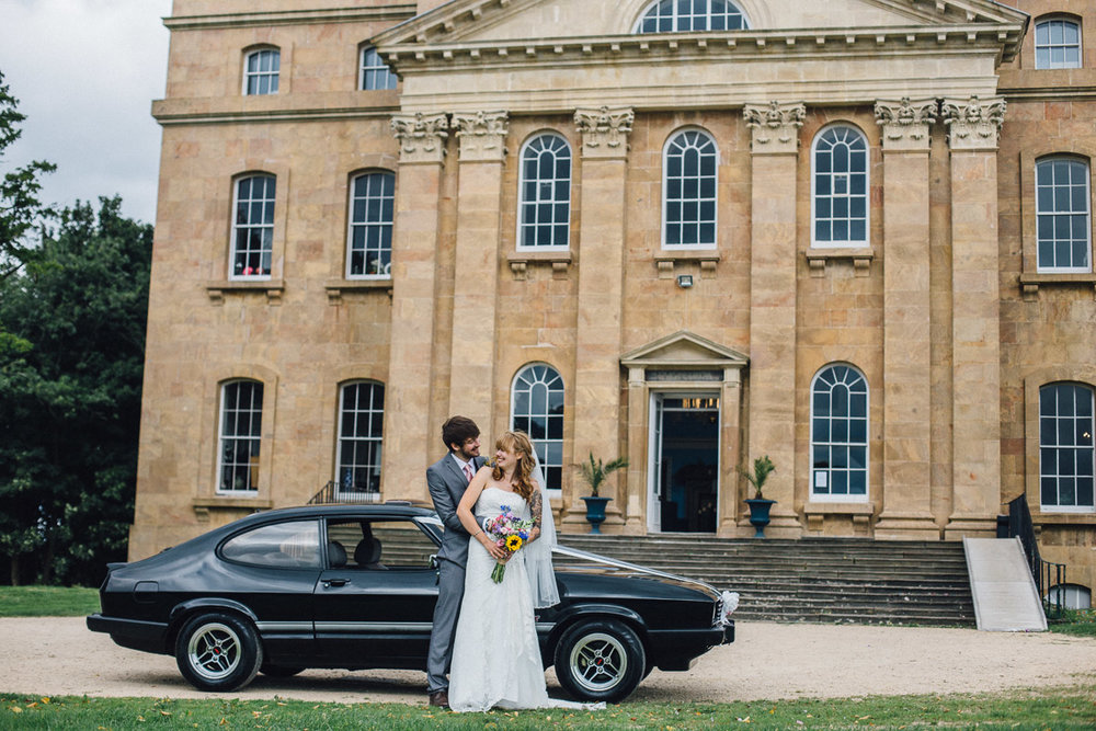 Bride and Groom Pose by Alternative Wedding Car outside Kings Weston House