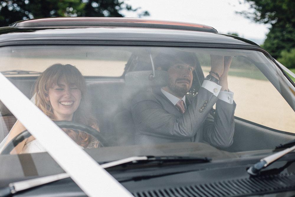 Bride Pretending to drive wedding car groom looks scared