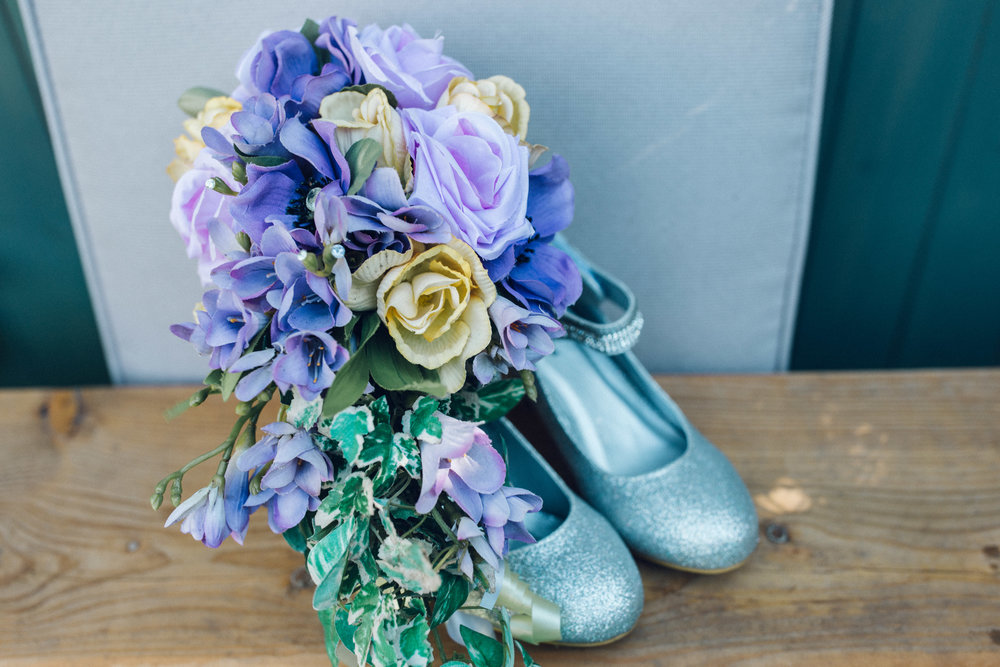 Pastel coloured artificial bouquet and glittery bride shoes
