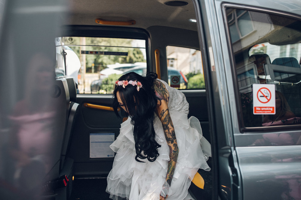 Heavily tattooed bride putting dress on