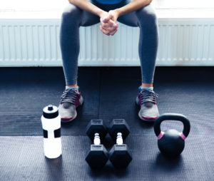 Closeup image of a woman sitting at gym with dumbbells, shaker and weight
