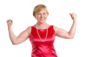 Portrait of fit senior woman flexing her biceps against white background. Laughing woman proud of herself.