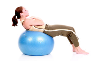 Woman doing situps on an exercise ball.