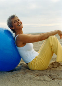 Woman Leaning on Exercise Ball --- Image by © RCWW, Inc./Corbis