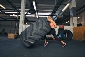 Fit female athlete working out with a huge tire turning and flipping in the gym. Crossfit woman exercising with big tire.