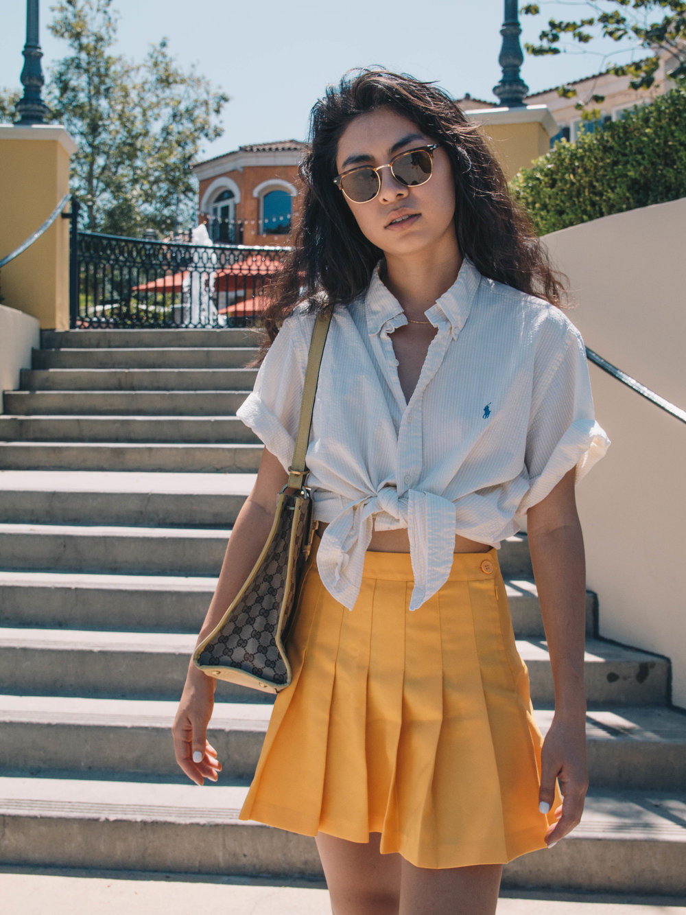 sister sunshine - this yellow button down is roomy, comfy, and 100% cotton. whether it's tucked into a pair of denim shorts or tied up into a crop top, it's become my go-to piece for all things casual. the best part? it was free- thanks for letting me steal it, dad!button down shirt - 2nd hand (ralph lauren polo)tennis skirt - american apparelwhite sneakers - chuck taylorpurse - vintage