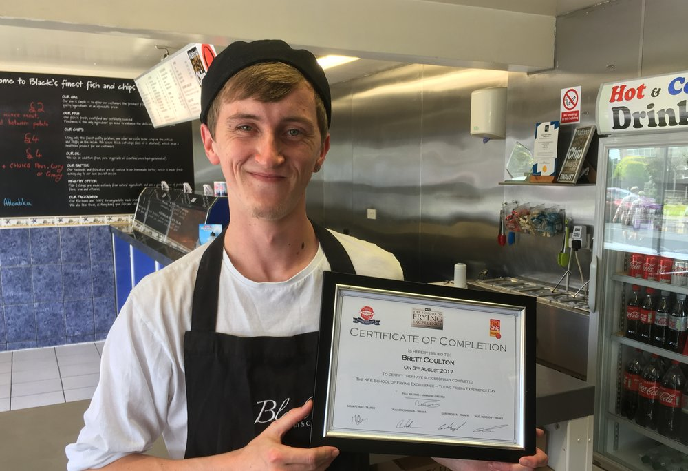 Brett Coulton of Black's Finest Fish & Chips, proudly sporting his certificate from the KFE School of Frying Excellence.