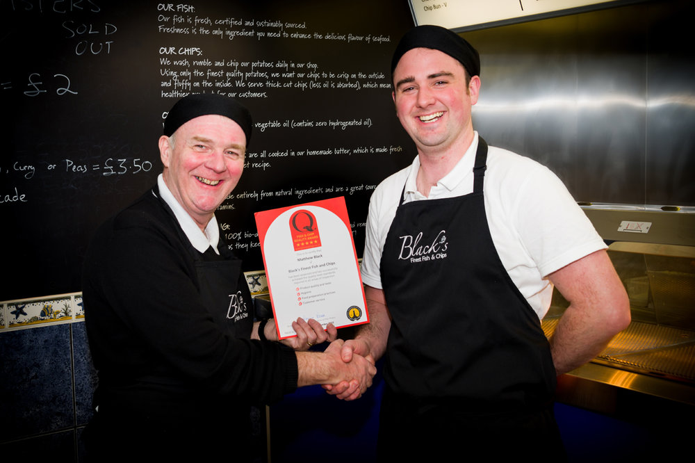 Matthew from Black's Finest Fish and Chips is presented with the NFFF Quality Award by John 'Gilly' Gilmore from BBC Radio Lancashire.