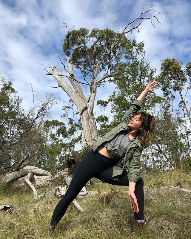 TAKE A HIKE: My spouse and I were goofing around on a hilltop during an afternoon hike in the Huon Valley when he took this photo - we hadn't seen a single person since we got on the trail but we had seen several echidnas so we were feeling giddy and silly. It was easy to strike a pose and feel sincere happiness. Peace. Ease. Gratitude. States that can be hard to access, emotions that are slippery and mediated and mysterious. I feel such simple relief in being outdoors and moving my body. We returned back from summer in Australia a few nights ago and the early darkness and cold have been a shock! Still, I am trying to spend as much time walking and breathing as possible.  I thought for a long time that being in striking distance to peace had to be complicated and expensive: the Wellness Industrial Complex is not a fucking joke. My 2018 started in a deep state of personal grief and professional exhaustion and intuitively I started taking short walks on my local trail and ceased trying every expensive healing modality and product around me. It was so transformative, even when I didn't have a lot of free time or energy, it was a salve to be connected to the earth and removed from exterior expectations. I still enjoy practicing yoga and giving and receiving reiki and breathwork, and I am lucky to be within a community of healers and experience their work with joy and openness, but I feel such a lack of the grasping that characterized the last couple of years. So, this is just a small reminder to trust and enjoy your intuition: as my teachers @davidelliott10 and @erintelford__ have expressed: healing can be simple, easy, even fun. ______________ #hiking #tasmania #huonvalley #yoga #outdooryoga #gooutsideandplay