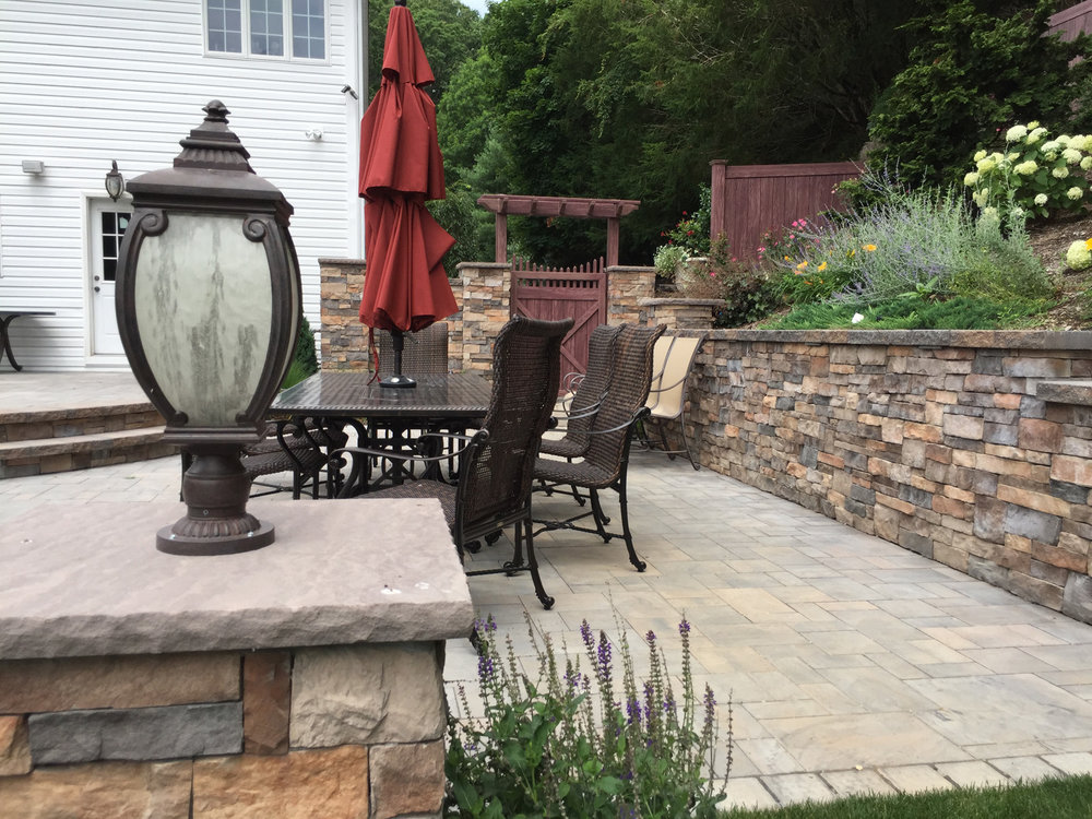 Professional landscape design with a paved patio in Long Island, NY