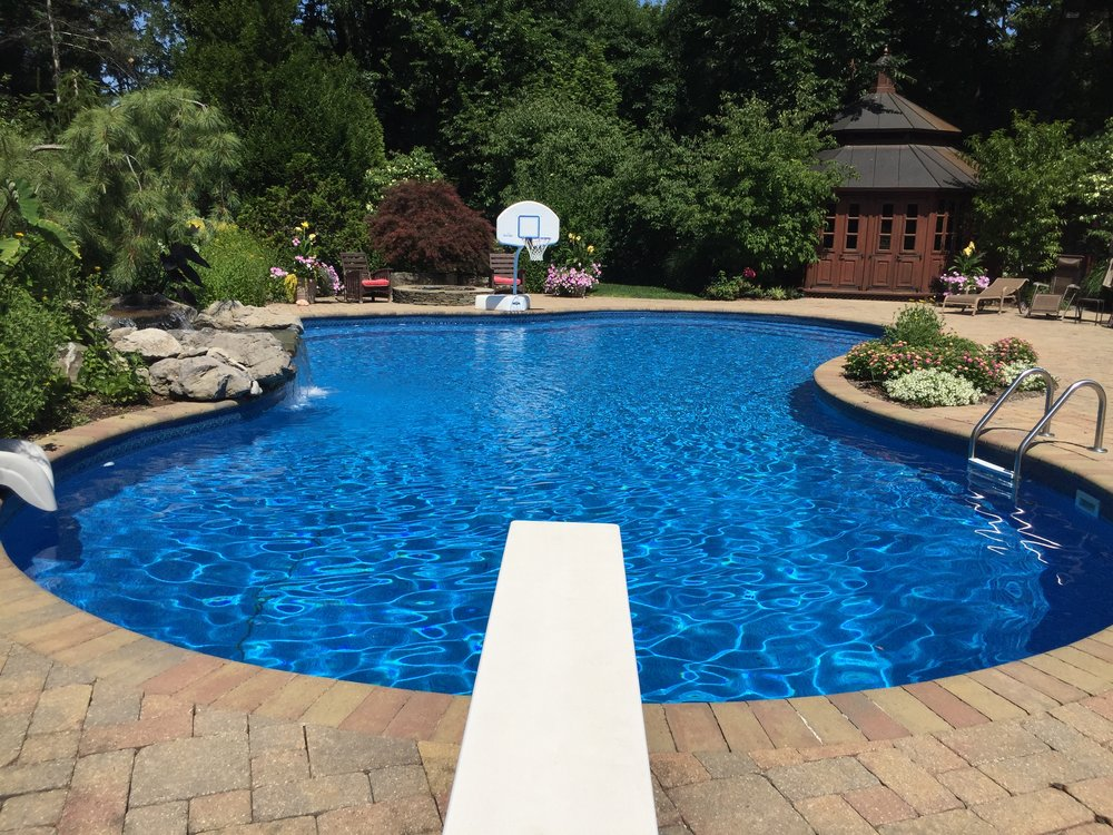 Top landscape design company with paved pool patio in Long Island, NY