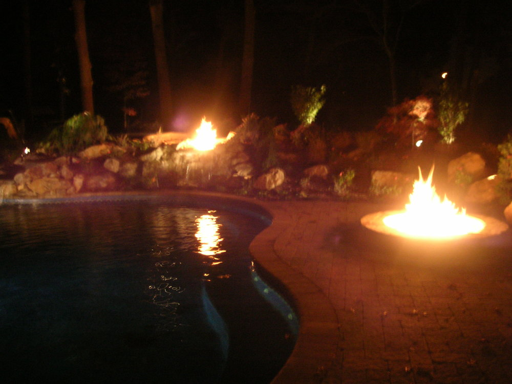 Landscape design with natural stone fire feature in Long Island, NY