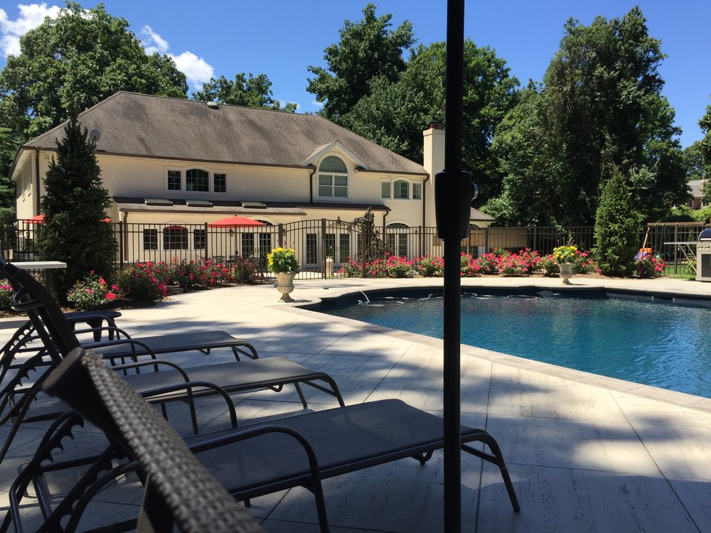 Professional landscape design with a paved pool patio in Long Island, NY