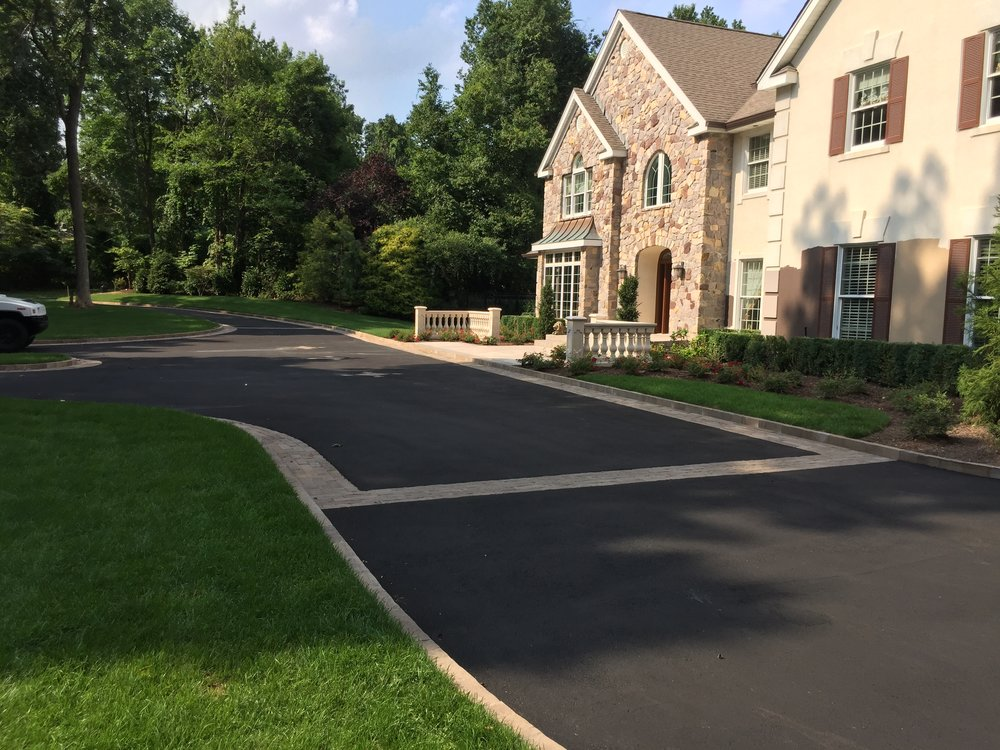 Professional landscape design with a paved driveway in Long Island, NY