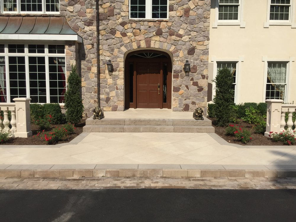 Professional landscape design with a paved entrance way in Long Island, NY
