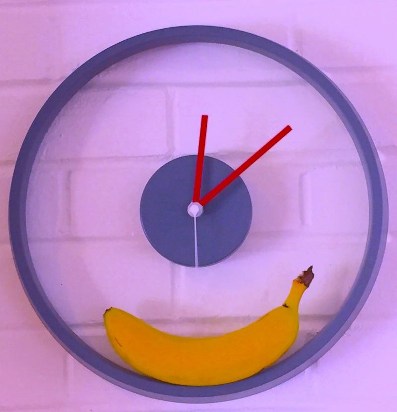 Wall clock with a banana resting on the bottom.