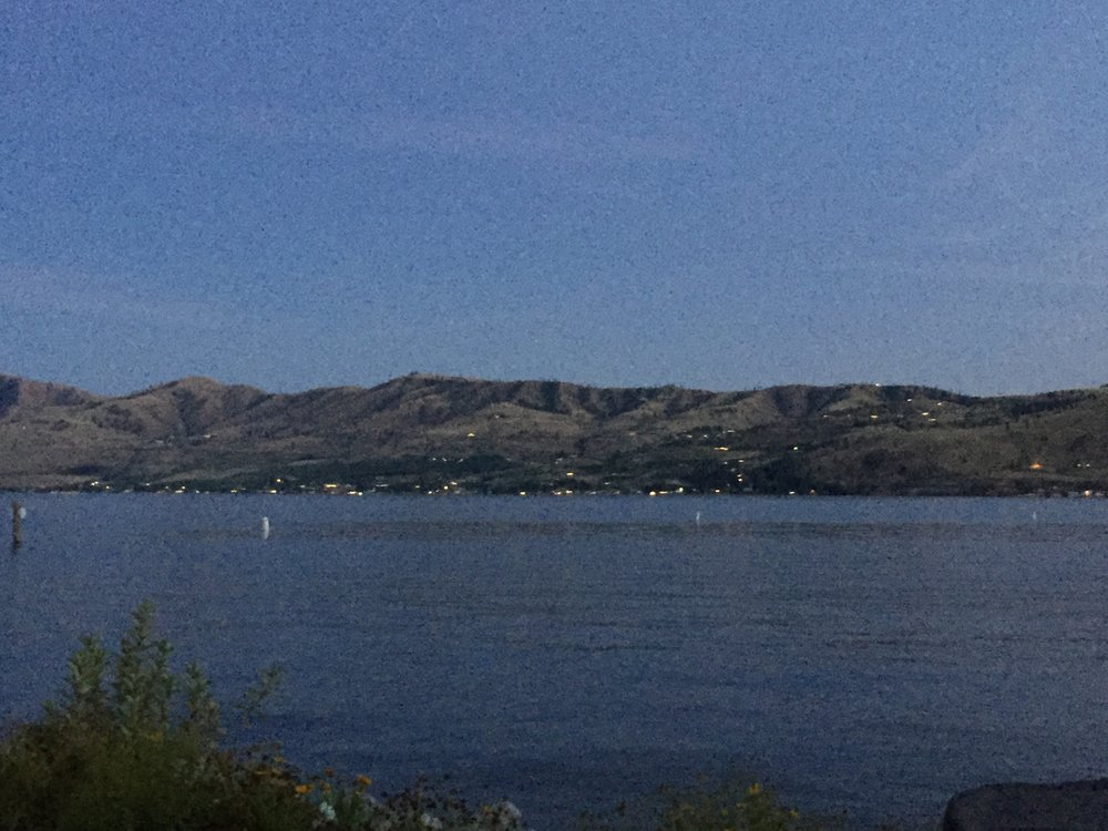 Lake Chelan with mountains in background and lights glittering.