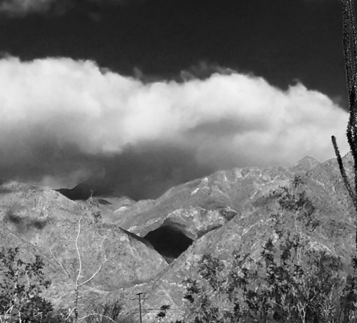 Black and white photo of mountains with clouds overhead.