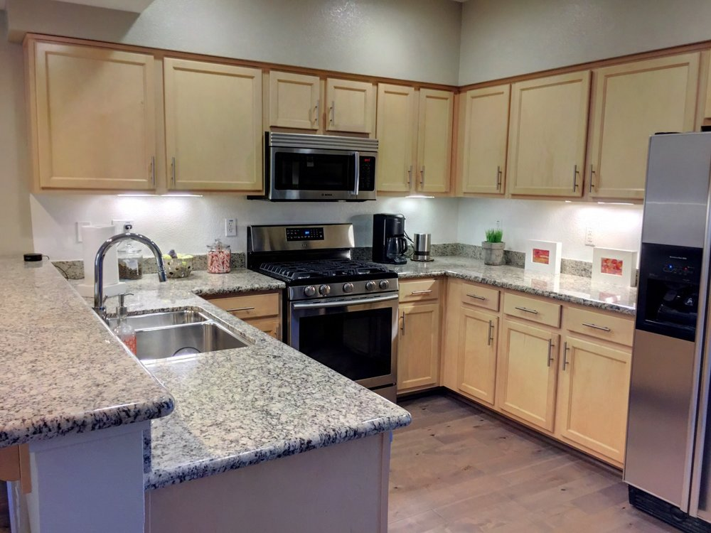 Gas range, stainless appliances and granite countertops in kitchen.