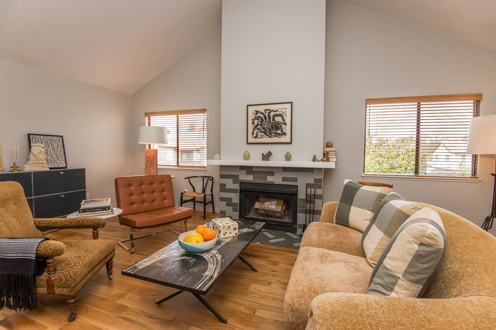 Spacious living area with new white oak flooing and refaced fireplace.