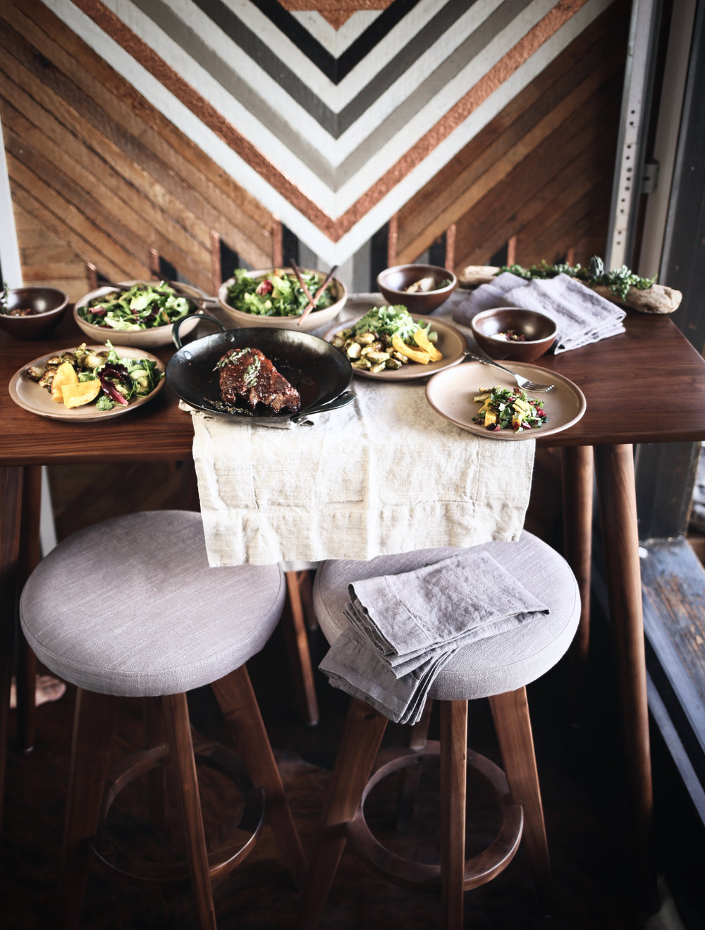 Table / stools : Article.  Table runner / napkins : Rough Linen.  Plates / Bowls : East Fork.  Pan : Blanc Creatives.