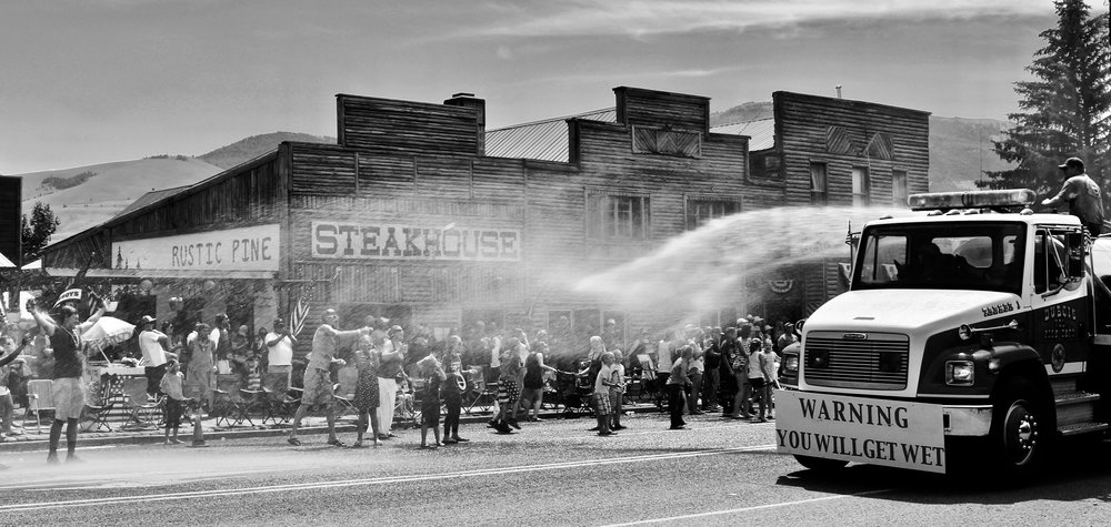 The town's firetruck sprays down the residents on a sweltering July day