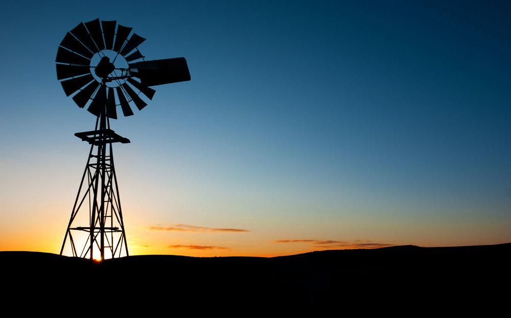 bigstock-Sun-rises-behind-a-windmill-15656000.jpg