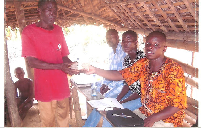 ere Emmanuel (in the orange shirt) is presenting David Bweh, the owner of the land, with the first check. (Also pictured are Emmanuel Sumo, the art teacher at the Vine School System of Christ, and Prince, a friend and member of the church)
