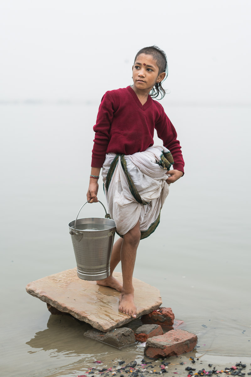The image of this young boy was taken at the banks of the River Ganga in Varanasi. I was out on a photowalk, early on a foggy morning. I had been walking upwards of an hour when I encountered this boy walking down the steps of the bank to the river. He was collecting water from the river to take to the temple, he was one of the young boys working there as the priest's apprentice. He had a dignified aura and his gait suggested grace far surpassing his years. Taking his picture was a gentle and wordless interaction, at the end of it we smiled at each other and parted as strangers.