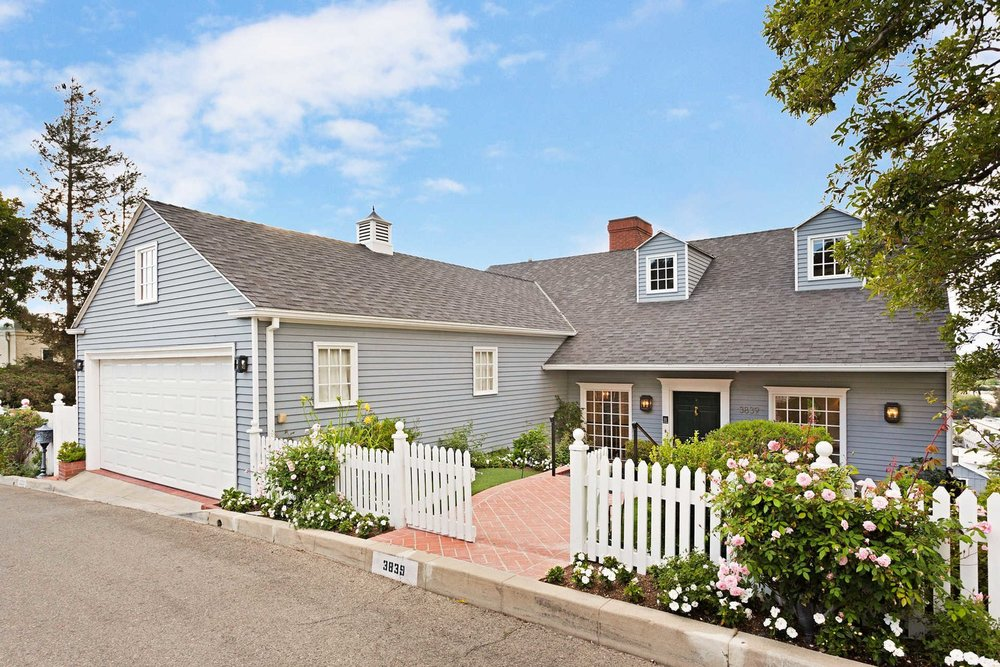 The home's charming New England-style facade and traditional picket fence lush with roses.