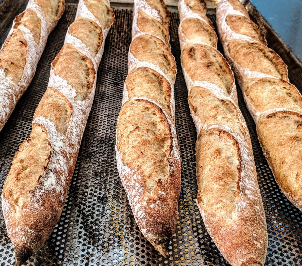 Plain Baguette - Our plain sourdough is shaped into these beautiful and delicious baguettes, perfect for soups, sides, cheese, olive oil, and your favorite spread. A great dinner party addition, they're moist on the inside, with the right amount of crunch on the outside.