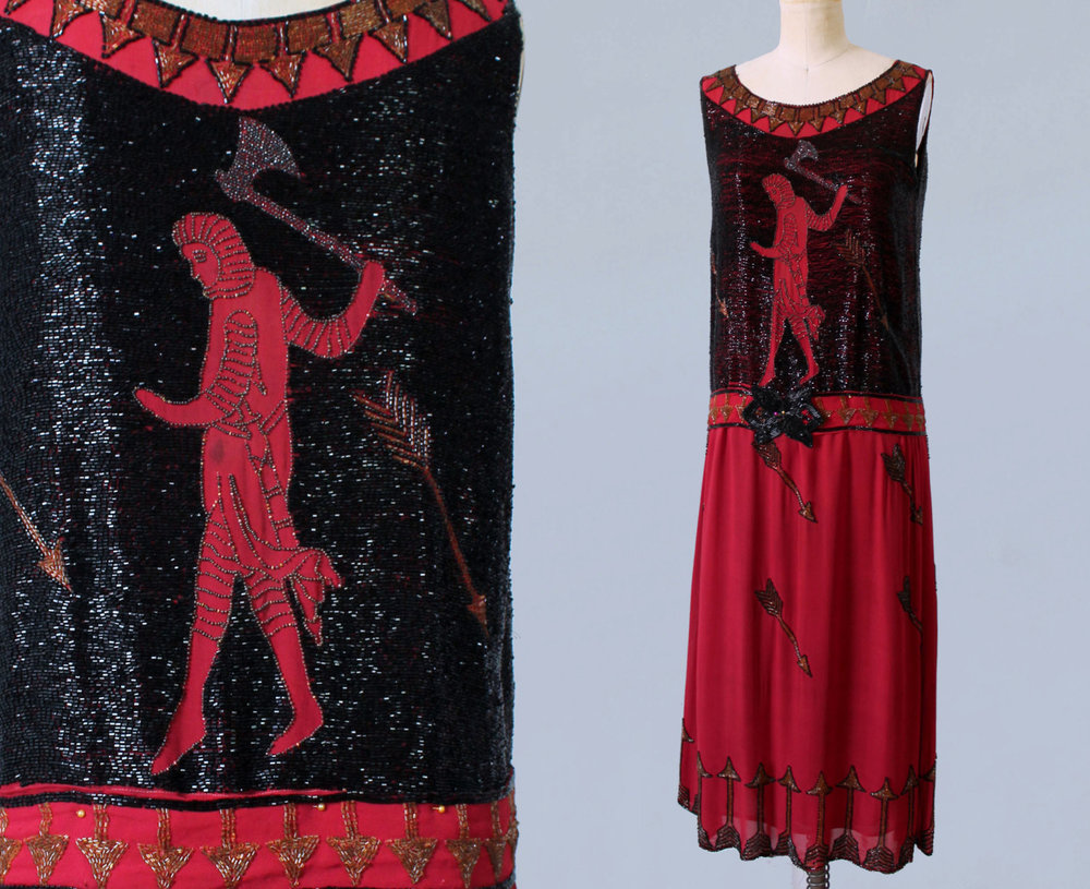 Red silk dress with densely beaded bodice. Mythical figure wielding an axe, surrounded by arrows. 1920s.