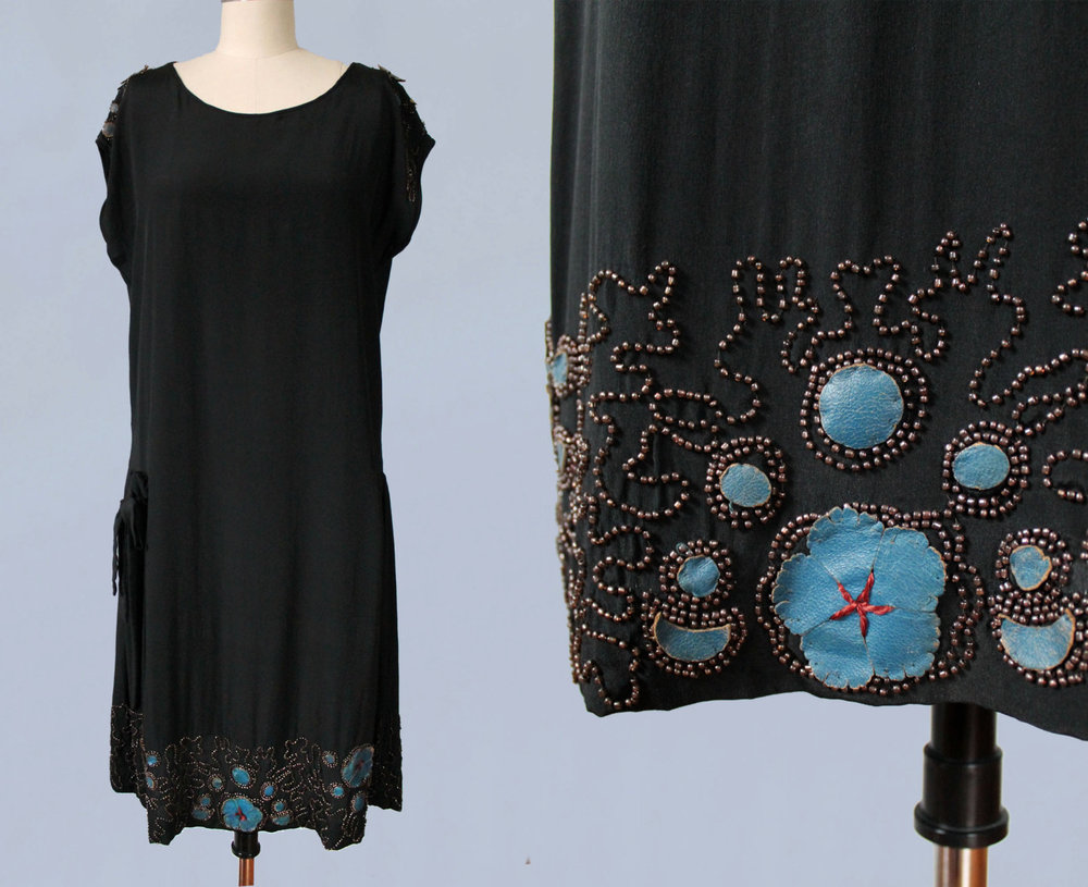 Black silk dress with beading and blue leather applique.