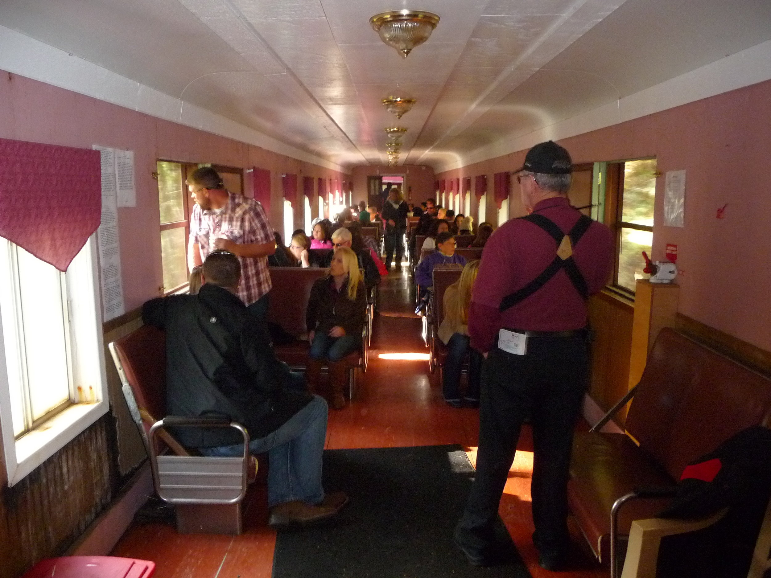 Passengers stretching out on the Chelatchie Prairie Railroad Wine Train as volunteer points out photo ops along the line