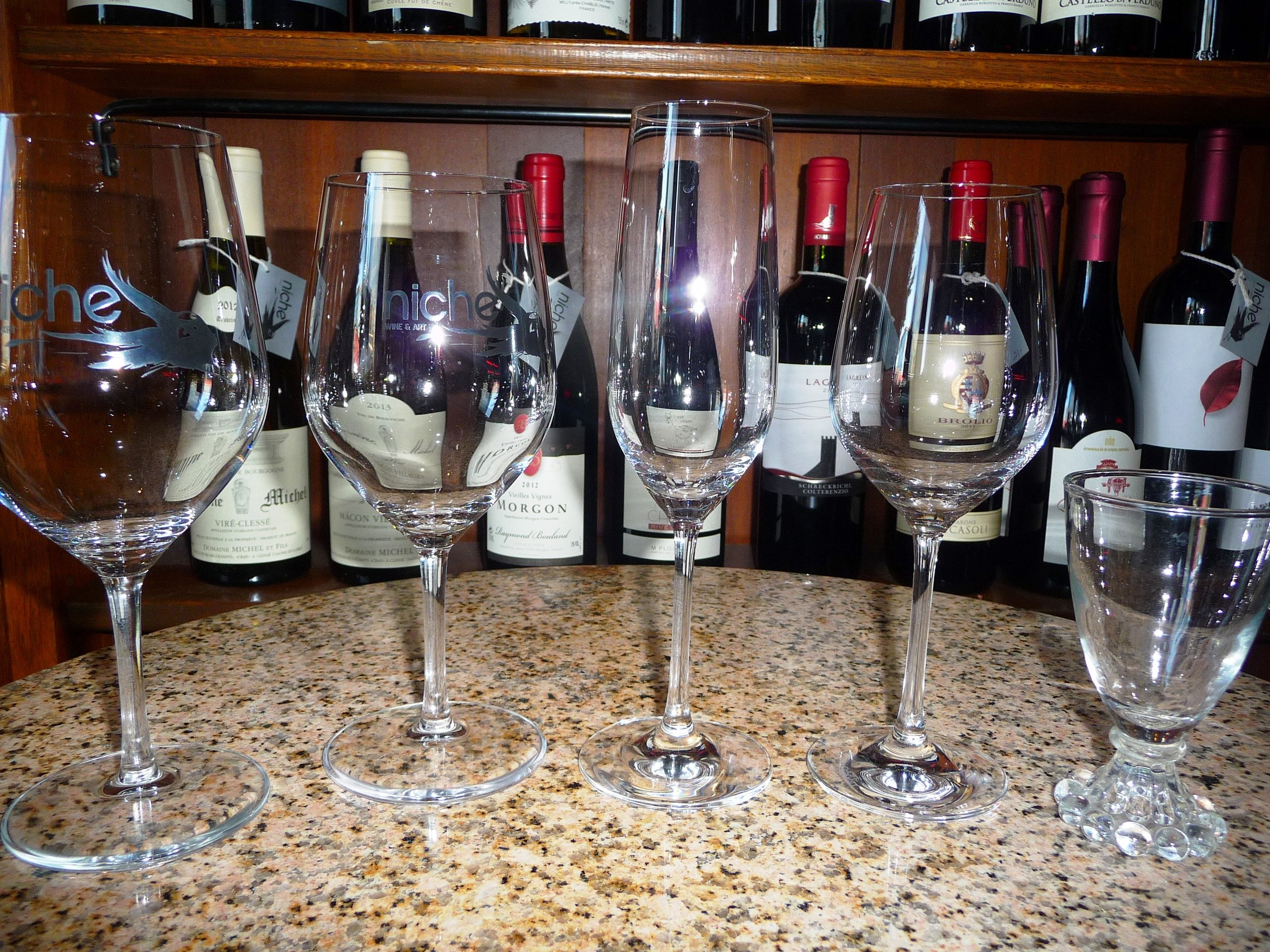 From left to right: 16 ounce red wine glass, 14 ounce white wine glass, Champagne flute, spirits wine glass with tulip shape to release aromas of Scotch for example, fun fortified wine glass for things like Port and Sherry.