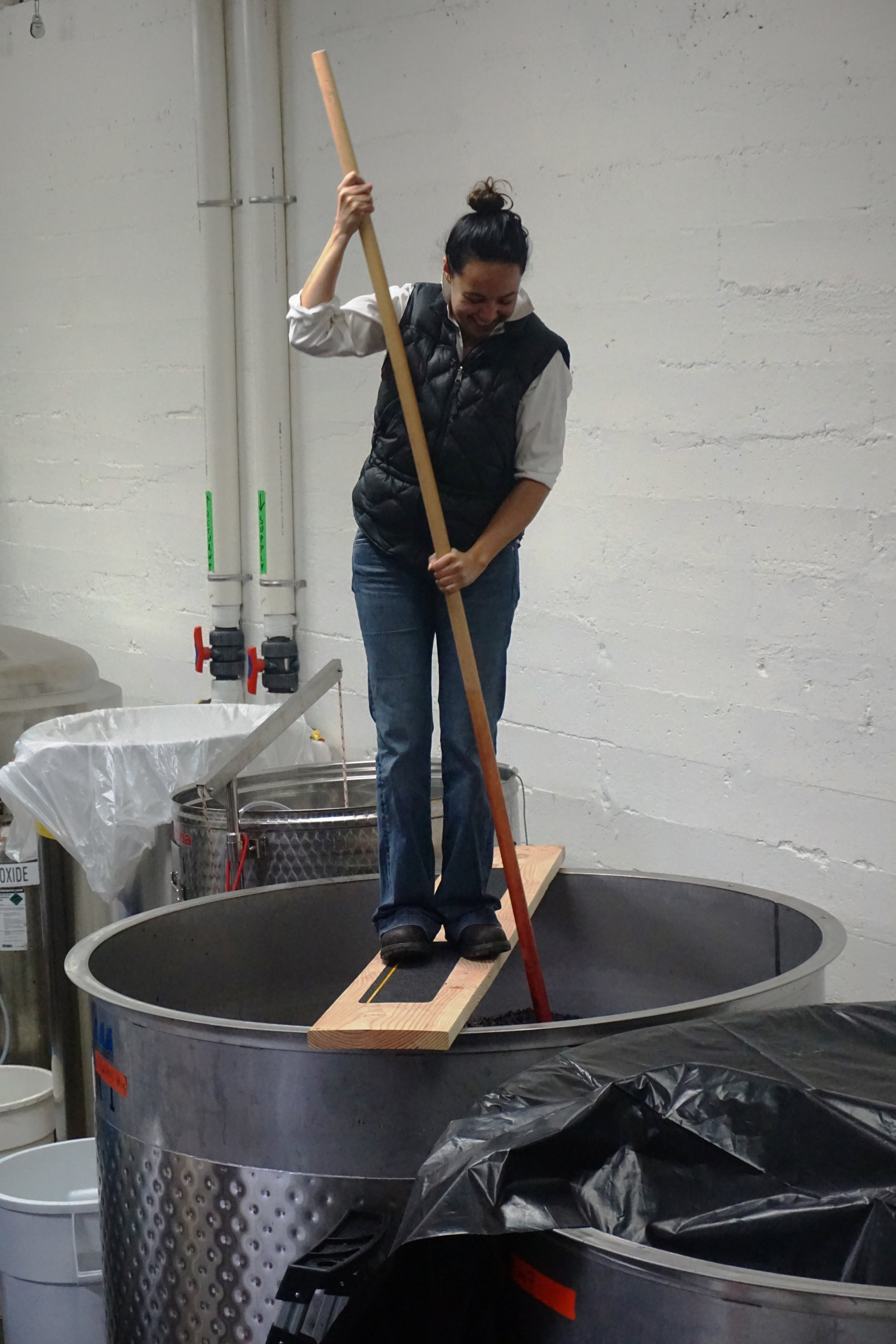 Norris has some serious abs and biceps to make punching down the grapes look as easy as she does. Standing a good six feet in the air on a foot-wide board with a plunger attached to a very long pole attempting to push it through the cap of grape solids that form on the top of the fermentation vessel with the bottom of the tank as the goal is a crazy core workout. Viki Eierdam