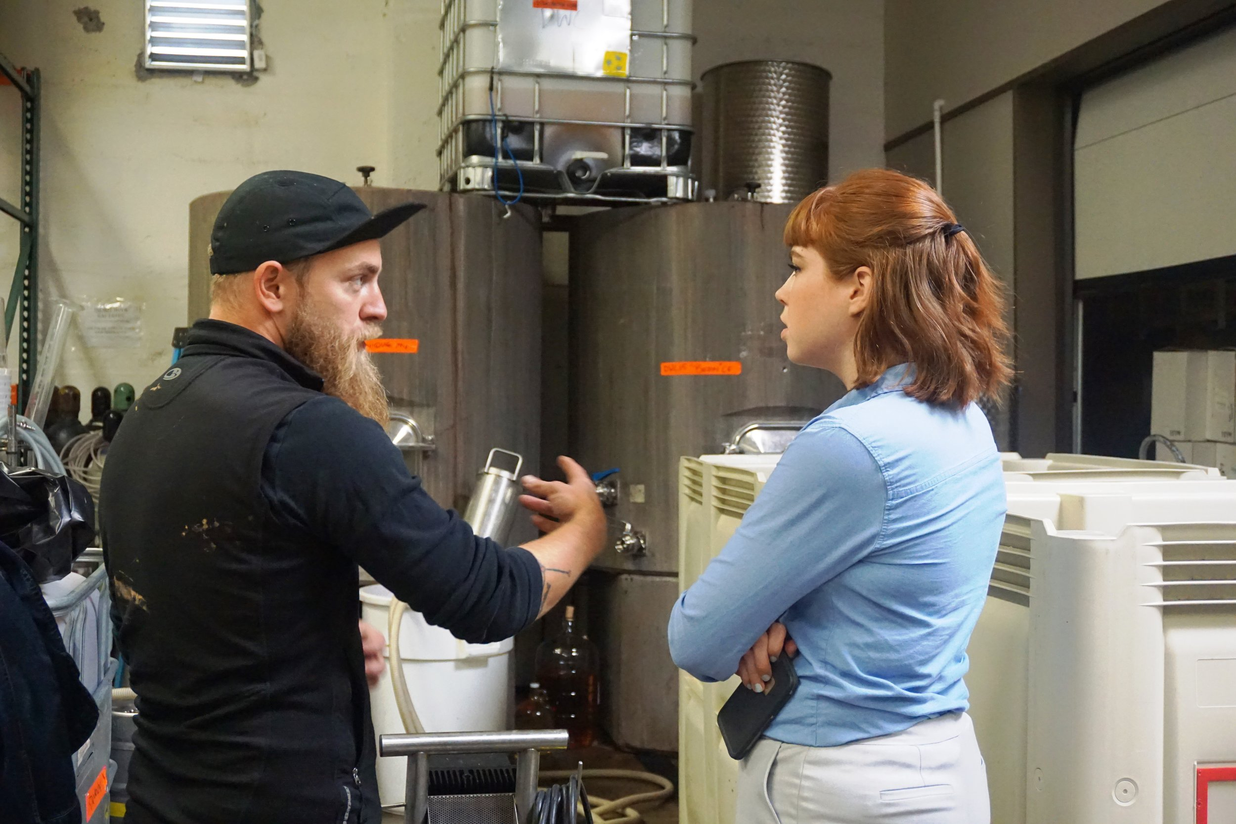 Luke Mathews, winery marketing & wine club specialist at SE Wine Collective, explains the concept of concrete fermenters to Jordan Johnson of Broussard Communications. Viki Eierdam