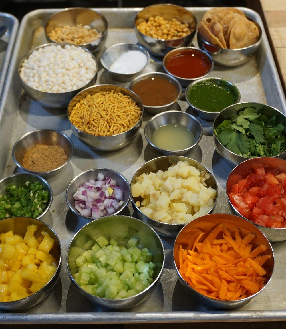 The ingredients that go into Bhel Puri, including from-scratch green chutney, tamarind chutney, fried chana dal, papri crackers chaat masala, sweet & hot and sev. Viki Eierdam