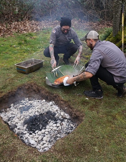 Chefs Chip Barnes and Brandon pull a perfectly cooked whole king salmon out of a makeshift fire pit and onto a fresh bed of banana leaves. Viki Eierdam
