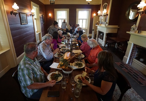 In the background, Chef Capers Ogletree introduces the main course to attentive diners at a recent Sunday Supper at The Eatery at the Grant House – Cedar Plank Salmon accompanied by a blackcap berry sauce and garnished with fir sprigs. Courtesy of Viki Eierdam