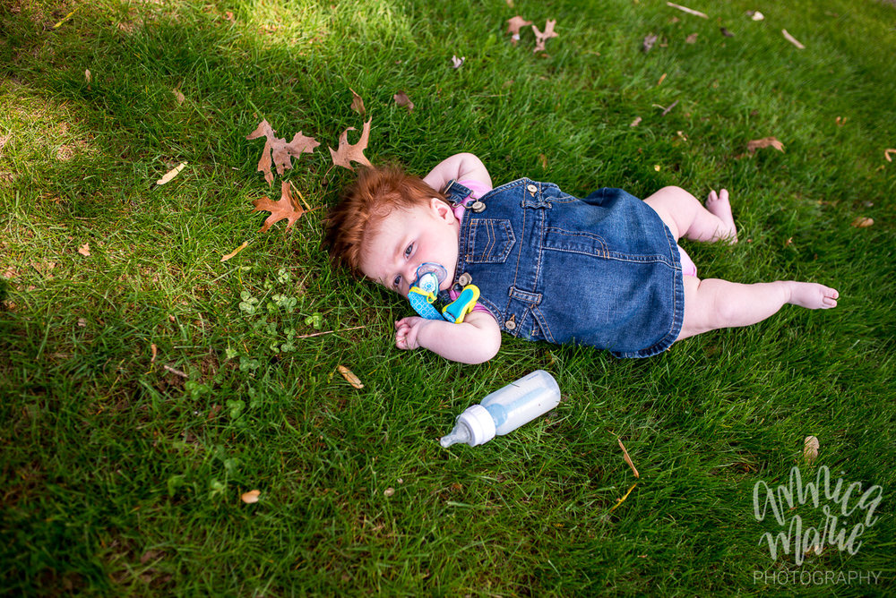 red haired baby and bottle in the grass