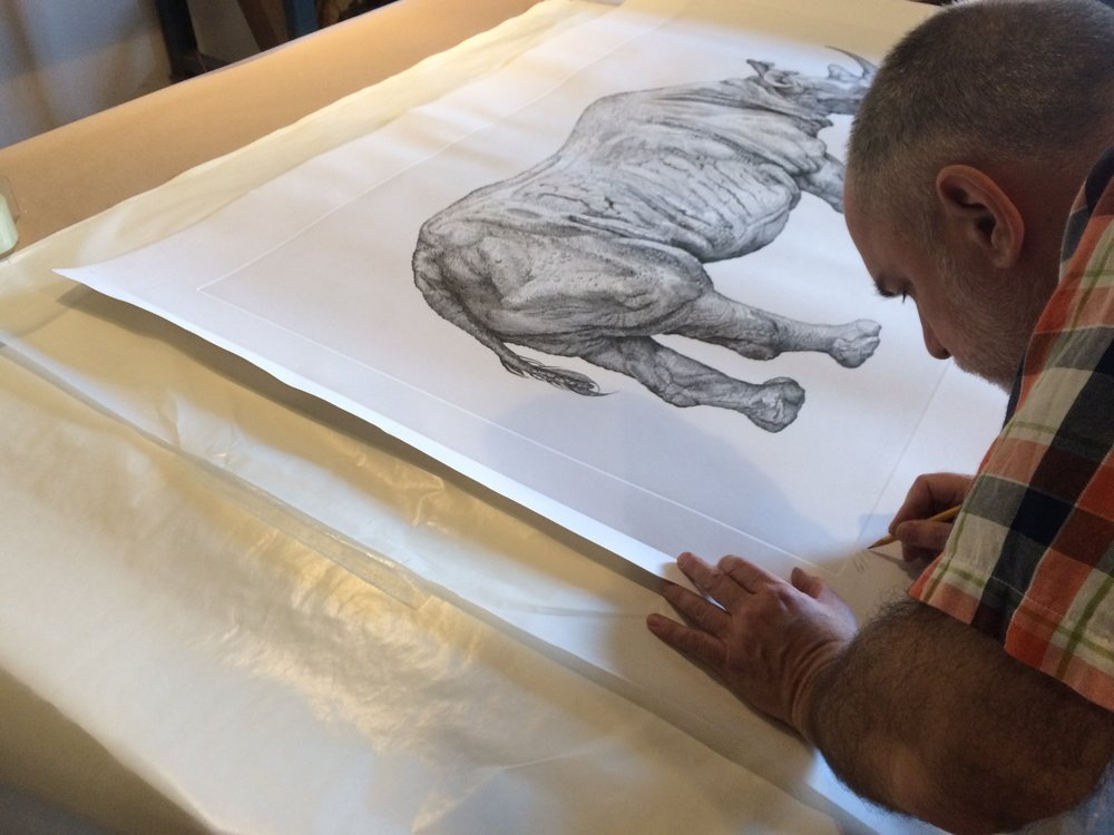 David signing a collasal Rhinoceros print.