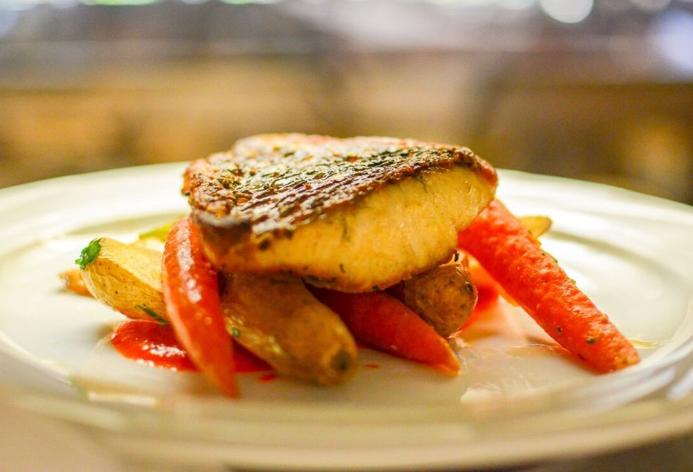 Barramundi Pan roasted over root vegetables and a roasted red bell pepper shallot sauce.jpeg
