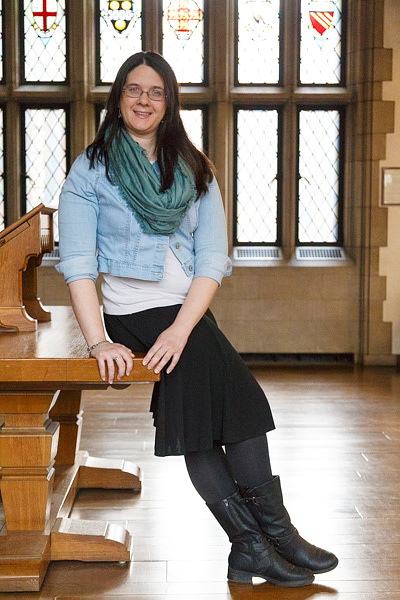 Creator Kit Englard leaning against a wooden table with large arched stain glass windows behind her. She has long brown hair draped over her shoulder, and is wearing a jean jacket and knee length skirt, looking over at the camera.