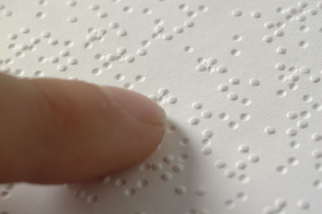 A single finger resting on a line of braille.