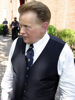 Actor Martin Sheen, playing Josiah Bartlet, is standing on the set of The West Wing. He is outside of St. Anne's Church. There is a row of greenery behind him.