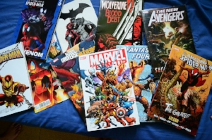 Marvel comics laying in a pile on a blue background.