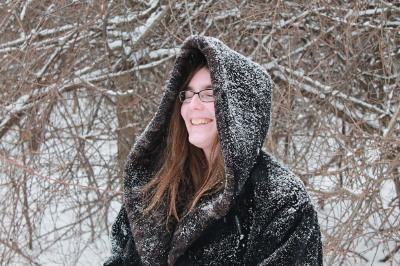 Ada Hoffmann standing in a winter forest. The trees behind her have snow, with brown bark peaking through. She is wearing a heavy black coat with the hood pulled up over her head. Her honey brown hair can be seen out of the front of her hood, framing a smiling face.