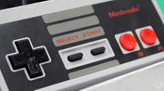 Image of the NES Classic Edition controller. It is rectangular, with the classic direction controller on the left, start and select in the middle, and A and B circle  action buttons on the right.