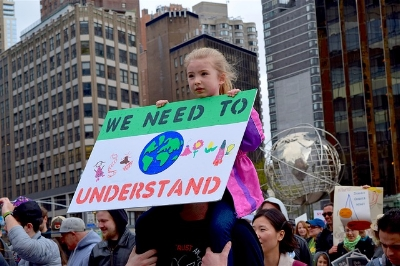 "Little girl sitting on someone's shoulders at one of the March for Science events, holding a sign which reads, ""We need to understand."""